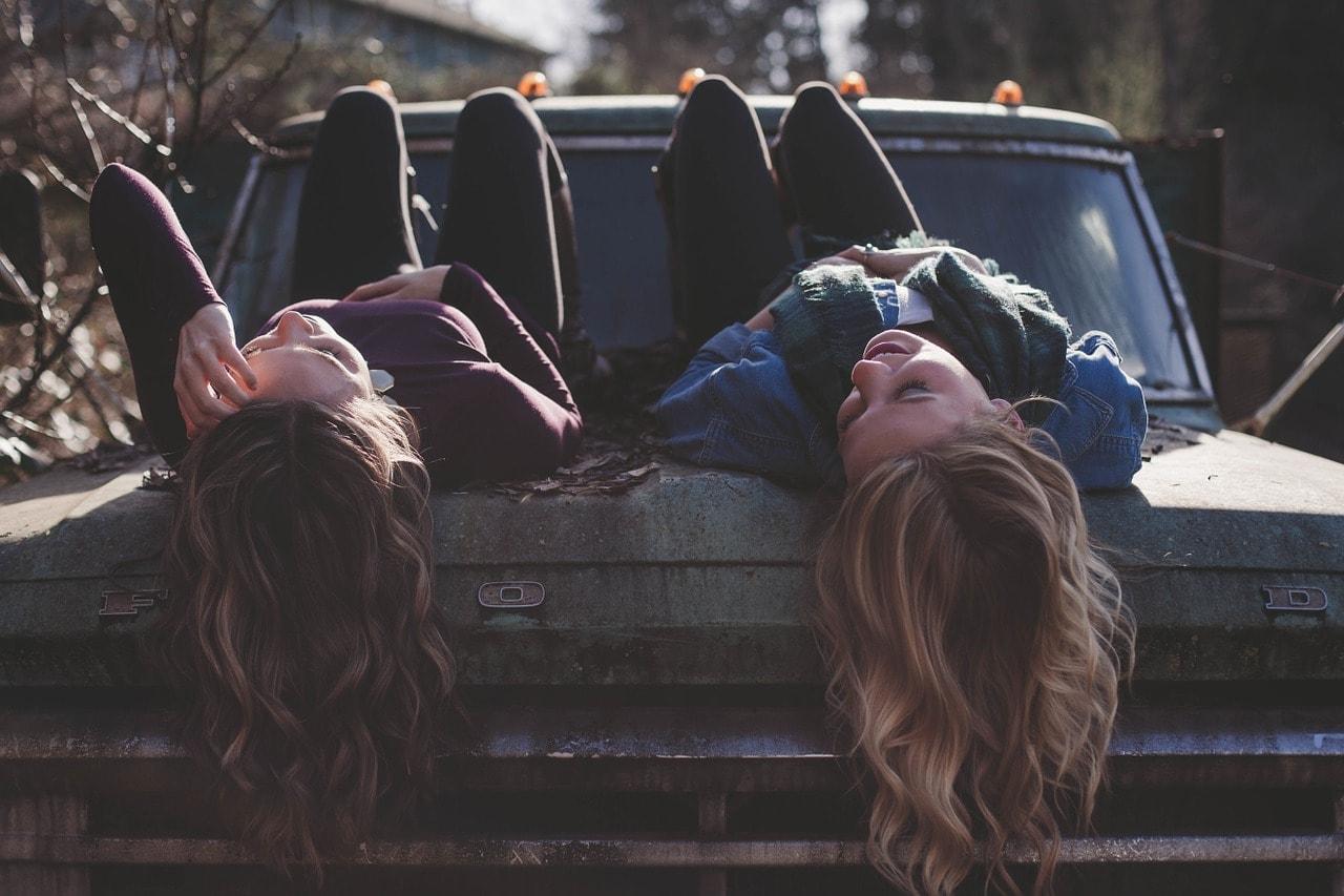 Junge BFFs entspannen auf einem Auto